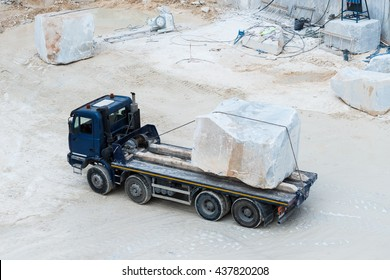 Marble truck carrying marble block / Marble truck with white marble block in Carrara quarry Italy / Carrara marble block in marble truck from above