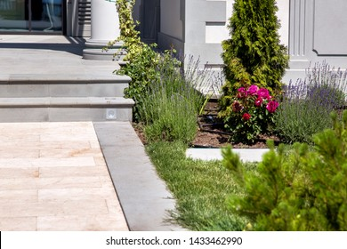 marble walkway with flowerbed at the entrance to the house with stone steps on a sunny summer day, details of the backyard with landscape design and architecture of the house.