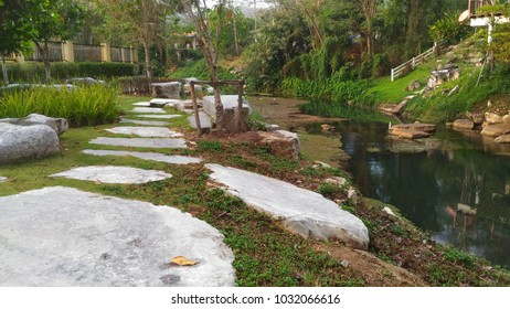 marble walkway as parallel with river in garden