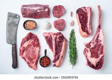 Marbled beef meat steak cut set, tomahawk, t bone, club steak, rib eye and tenderloin cuts, on white stone background, top view flat lay