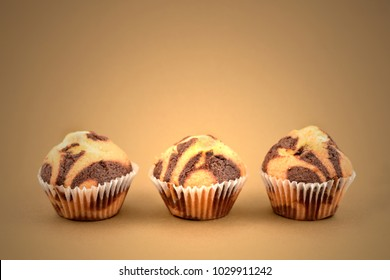 Marbled chocolate muffins stock images. Muffins on a brown background.  Three muffins isolated on a brown background