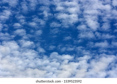 Marbled cloud shape in an intense blue sky. Natural background.