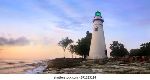 The Marblehead Lighthouse Bathed In The First Light Of Dawn On A Foggy Morning Over Lake Erie At Marblehead Ohio, USA