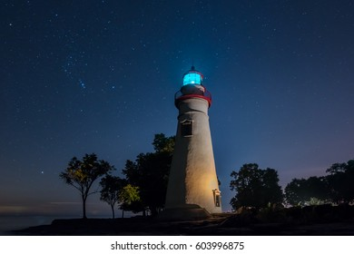 Marblehead Lighthouse in Ohio with light on and stars glowing