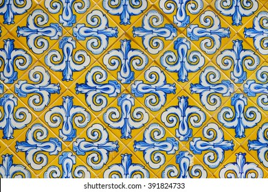 Marble-stone mosaic texture. Ornamented tiles texture background. ancient Spanish, european yellow and blue mosaic, Picturesque Europe city wall.
