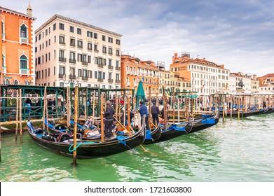 March 03, 2014: Riva degli Schiavoni, its facades and gondolas with tourists in Venice in Veneto, Italy