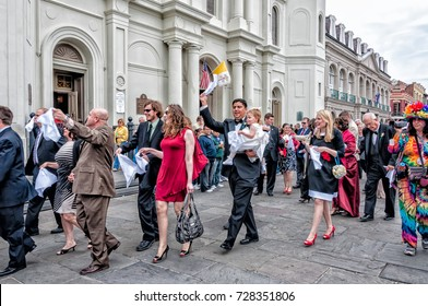March 10, 2012 A post-wedding second-line parades in front of St. Louis Cathedral in the French Quarter. Some people are waving white handkerchiefs. This is tradition in some New Orleans LA weddings.