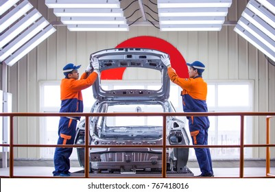 March 14, 2017 Chinese workers Zhang Quan and Li Ming are checking the outer frame of the car, representing the latest advanced level in China's auto industry