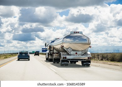 March 15 2018 Lost Hills / CA / USA - Tanker truck driving on interstate I5, the road being reflected in its shiny cistern;