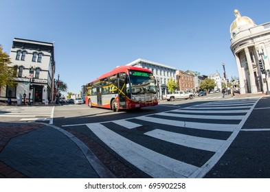 MARCH 16 2017 - GEORGETOWN, WASHINGTON DC: A DC Circulator bus crosses into a pedestrian crosswalk as it drives through the Georgetown neighborhood. Fisheye view.