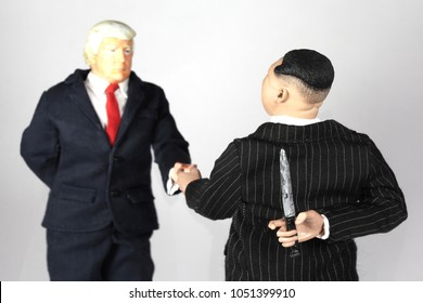 MARCH 16 2018: Caricatures of US President Donald Trump and North Korean Supreme Leader Kim Jong Un shaking hands under truce, with Kim holding a knife behind his back, betrayal concept
