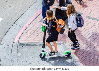 March 19, 2019 San Diego / CA / USA - Aerial view of young woman riding a lime scooter in downtown San Diego