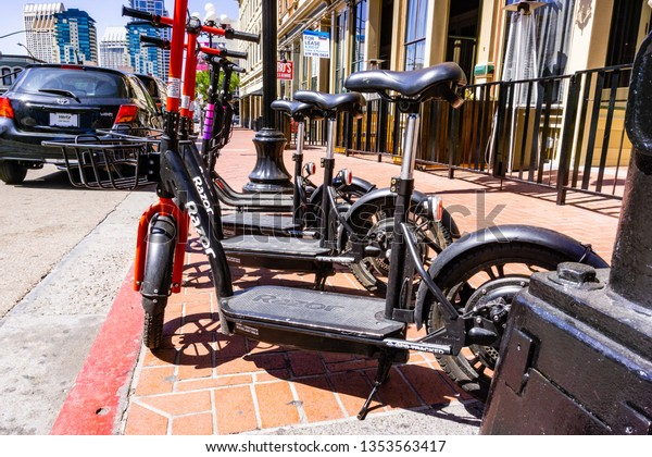 March 19, 2019 San Diego / CA / USA - Razor Share and Lyft Escooters parked side by side on the sidewalk in downtown San Diego