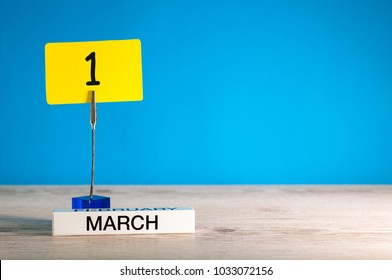 March 1st. Day 1 of march month, calendar on little tag at blue background. Spring time. Empty space for text, mockup