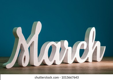 March - 1st month of spring. Wooden carved word at dark blue background. Card for Mothers day, 8 March, Easter