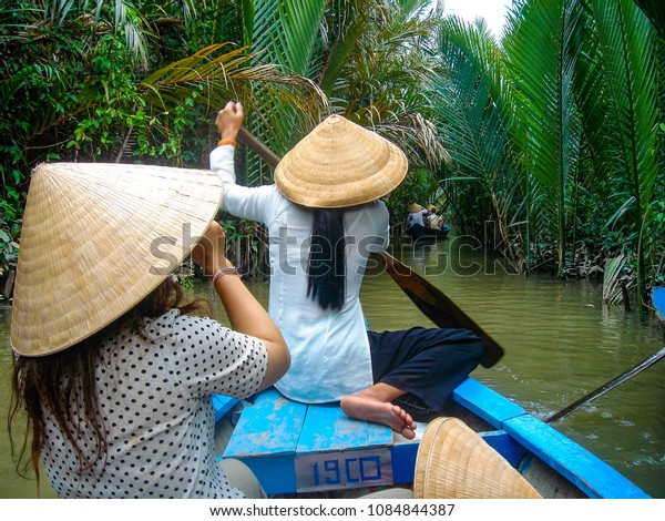 March 2, 2009 - Ho Chi Minh, Vietnam: A Vietnamese lady wearing a traditional conical hat, sits on her wooden boat in the Mekong Delta