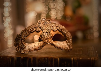 March, 2019 - Bucharest, Romania: A close up of a venetian lace mask with vintage patina on and an old brown book with bokeh background.