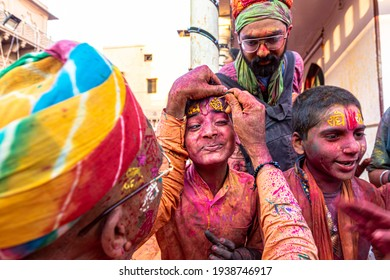 march 2021 mathura,india. a man puts colors on holi festival in india with selective focus on subject and added noise and grains.