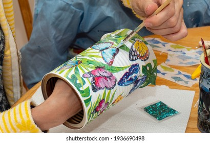 March 2021, Tampa, FL - Skilled artists hands applying lacquer to an Arts and crafts decoupage project using napkins with kids