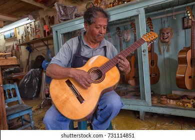 March 21, 2014 Paracho, Mexico: a luthier in the famous guitar making town demonstrating the sound of one of the instruments his shop produced