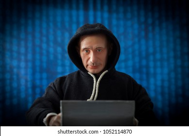 MARCH 21 2018: Caricature of Russian President Vladimir Putin in an election hacking concept - in a dark hoodie, at a laptop with binary code