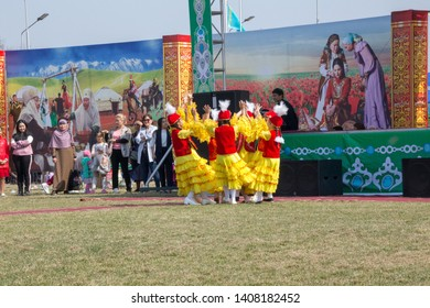 March 22, 2019 Almaty, Kazakhstan. Girls' groups dance in national costumes at the stadium during the celebration of the Nauryz holiday