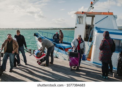 MARCH 24th, 2018 - OLHAO, PORTUGAL: People getting down from a boat and arriving to Armona Island, in Portugal, after the trip navigating Ria Formosa from Olhao city, on March 24th, 2018.