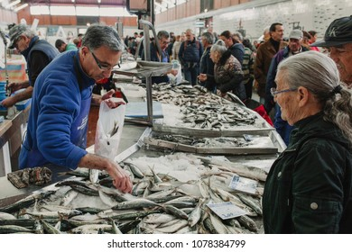 MARCH 24th, 2018 - OLHAO, PORTUGAL: Fishmonger selling fish to a client at the fish market in Olhao, Portugal on March 24th, 2018.