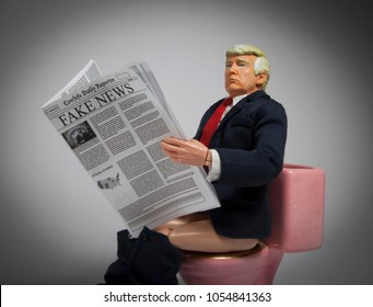 MARCH 25 2018: Caricature of United States President Donald Trump having his Executive Time - reading a Fake News newspaper while sitting on the toilet.