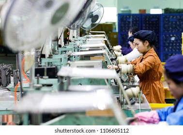 March 30, 2018: a beautiful young girl operates a machine in the workshop production line, winding a copper wire to make a small engine. A sweaty electronics factory in Jiujiang, East China's Jiangxi.