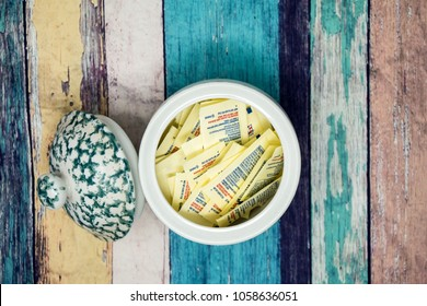 MARCH 30 2018 - MINNEAPOLIS, MN: An opened jar filled with artificial sweetener packets sits on a colorful wooden plank background
