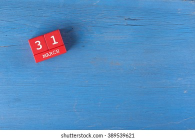 March 31, Cube calendar on wooden surface with copy space