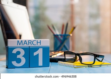March 31st. Day 31 of month, calendar on business office background, workplace with laptop and glasses. Spring time, empty space for text