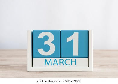 March 31st. Day 31 of month, daily calendar on wooden table background. Spring time, empty space for text
