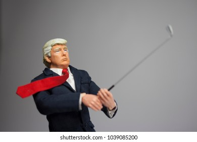 MARCH 4 2018: Caricature of US President Donald Trump swinging a golf club. Golfer In Chief concept using an action figure.