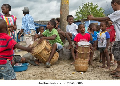 March 8, 2015 Sambo Creek, Honduras: young garifuna boys playing traditional drums outdoors in the center of their village