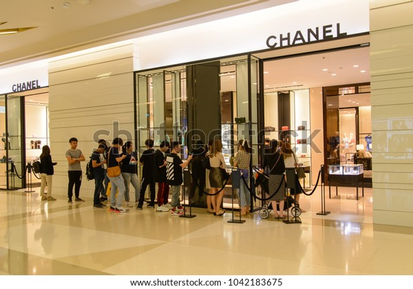 March 9, 2018. Wide angle view of a group of Chinese tourists queuing up in front of a Chanel luxury French boutique. Siam Paragon, Bangkok, Thailand. Fashion industry editorial.