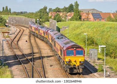 MARCH, CAMBRIDGESHIRE, UK - AUGUST 18, 2012: EWS-liveried DB Schenker Class 66 No. 66147 brings up the rear of a 6 loco convoy, as they enter Whitemoor Yard, with the 0X11 working out of Wembley Yard.