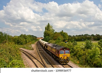 MARCH, CAMBRIDGESHIRE, UK -AUGUST 5, 2011: Against a dynamic sky, Euro Cargo Rail Class 66/0 No. 66249 heads west out of March with the Middleton Towers to Goole working with a train of loaded sand.
