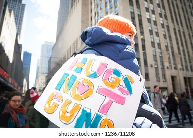March For Our Lives: A little boy sits on a mans shoulders with a sign that says Hugs Not Guns around his neck at the protest and national march to end gun violence, 6th Ave NEW YORK MAR 24 2018.