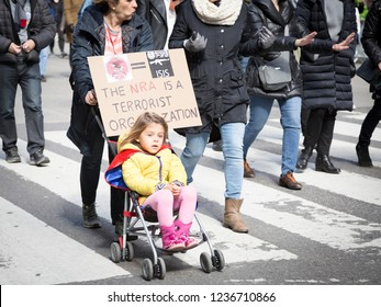 March For Our Lives: A little girl in a stroller pushed by a protester with a sign that says The NRA Is A Terrorist Organization at the national march to end gun violence 6th Ave NEW YORK MAR 24 2018.