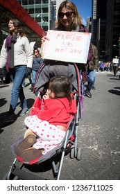 March For Our Lives: A little girl in a stroller pushed by a protester holding a sign that says Protect Kids Not Guns at the national march to end gun violence, 6th Ave NEW YORK MAR 24 2018.