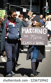 March For Our Lives: A man holding an infant child and woman with a sign Marching For Mira protest at the march on 6th Ave to end gun violence, NEW YORK MAR 24 2018.