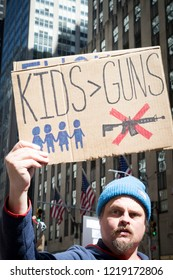 March For Our Lives: A man holds a sign that says Kids > Guns during the march to end gun violence on 6th Ave, NEW YORK MAR 24 2018.