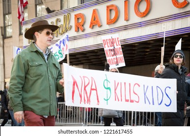March For Our Lives: Participants in the march to end gun violence hold signs with various phrases including NRA $ Kills Kids, on 6th Ave, NEW YORK MAR 24 2018.