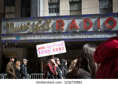 March For Our Lives: A protester in front of Radio City Music Hall holds a sign that says More Glitter Less Guns at the march on 6th Ave to end gun violence, NEW YORK MAR 24 2018.