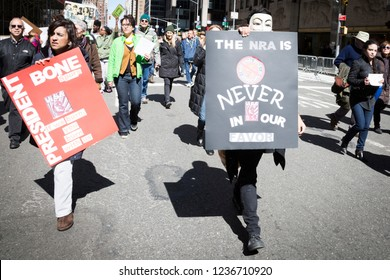 March For Our Lives: A protester wearing a Guy Fawkes mask holds a sign that says The NRA Is Never In Our Favor at the march on 6th Ave to end gun violence, NEW YORK MAR 24 2018.