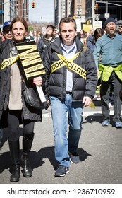 March For Our Lives: Protesters with yellow caution tape wrapped across their chests and on their sign questioning gun violence against children in the march on 6th Ave, NEW YORK MAR 24 2018.