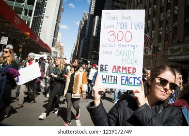 March For Our Lives: A woman holds a sign that references Sandy Hook school shooting and says Be Armed With Facts during the march to end gun violence on 6th Ave, NEW YORK MAR 24 2018.