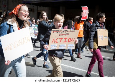 March For Our Lives: A young boy holds a sign that says Action underneath the words Thoughts and Prayers crossed out at the march to end gun violence on 6th Ave, NEW YORK MAR 24 2018.